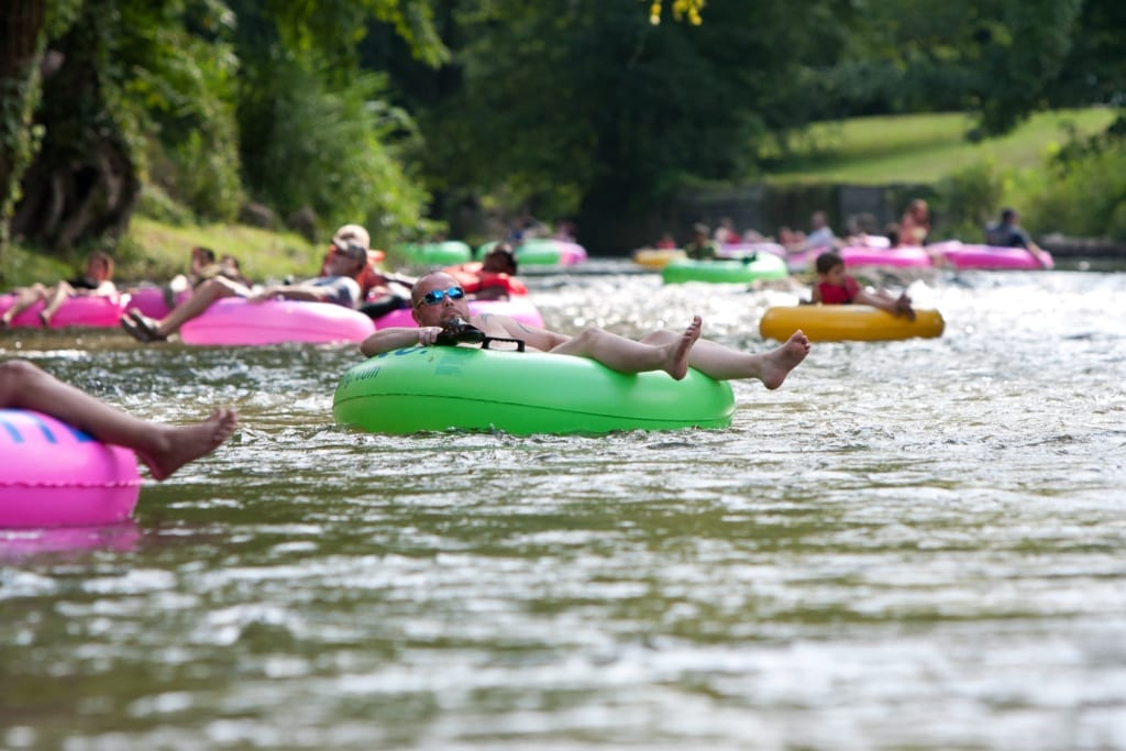 People lounging on assorted colors of inter tubes floating on a river.